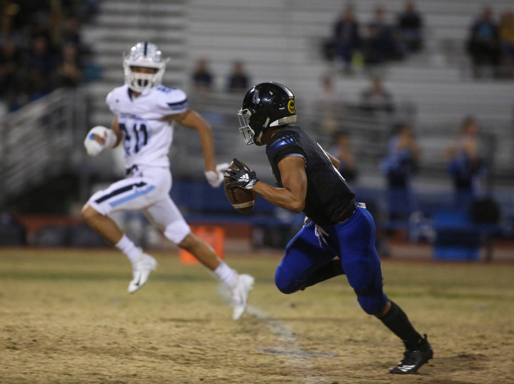 Desert Pines High School's Branden Thomas (4) runs with the ball as Centennial High School's Davone Walden Jr. (20) tries to catch up during the first half of a varsity playoff football game at De ...