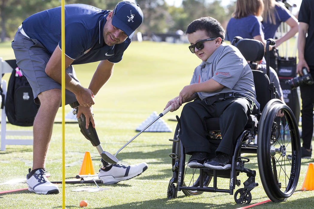 Shriners Hospital celebrity patient Alec Cabacungan, 16, putts while getting some pointers from US Adaptive Golf Alliance trainer John Bell during a golf clinic on day two of the Shriners Hospital ...