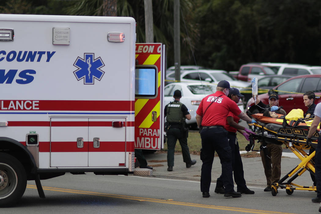A person is transported from scene of a shooting, Friday, Nov. 2, 2018, in Tallahassee, Fla. A shooter killed one person and critically wounded four others at a yoga studio in Florida's capital be ...