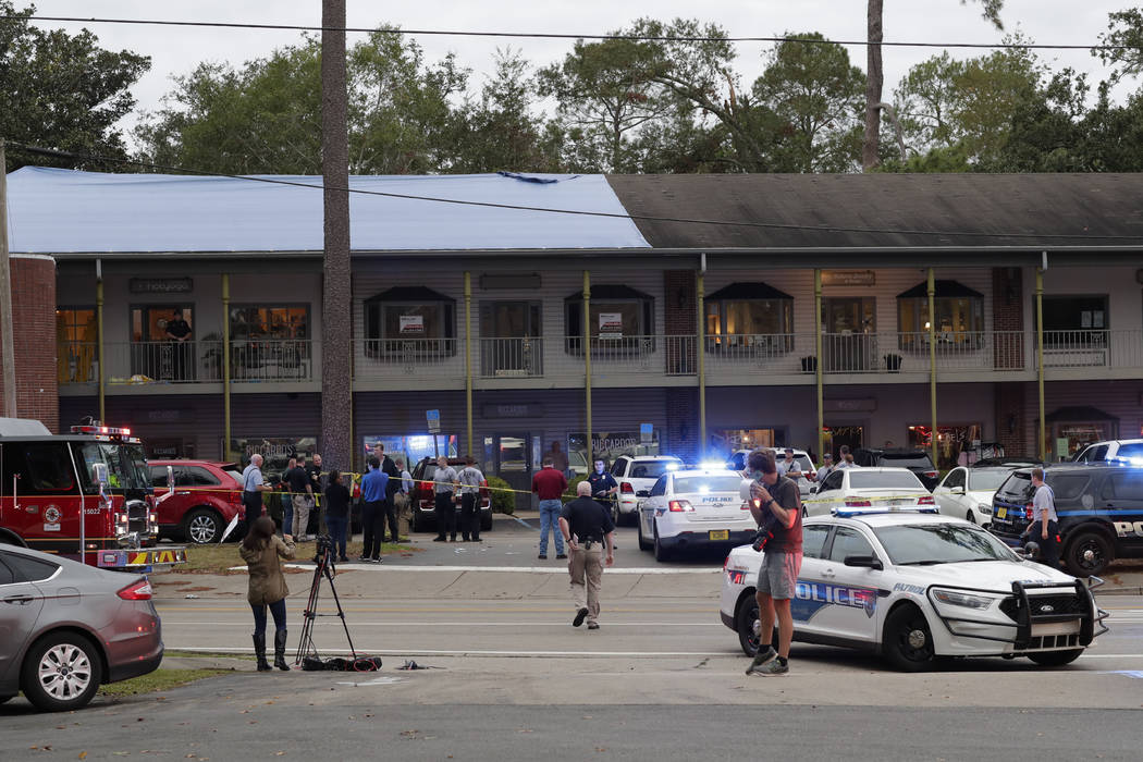 Police investigators work the scene of a shooting, Friday, Nov. 2, 2018, in Tallahassee, Fla. A shooter killed one person and critically wounded four others at a yoga studio in Florida's capital b ...