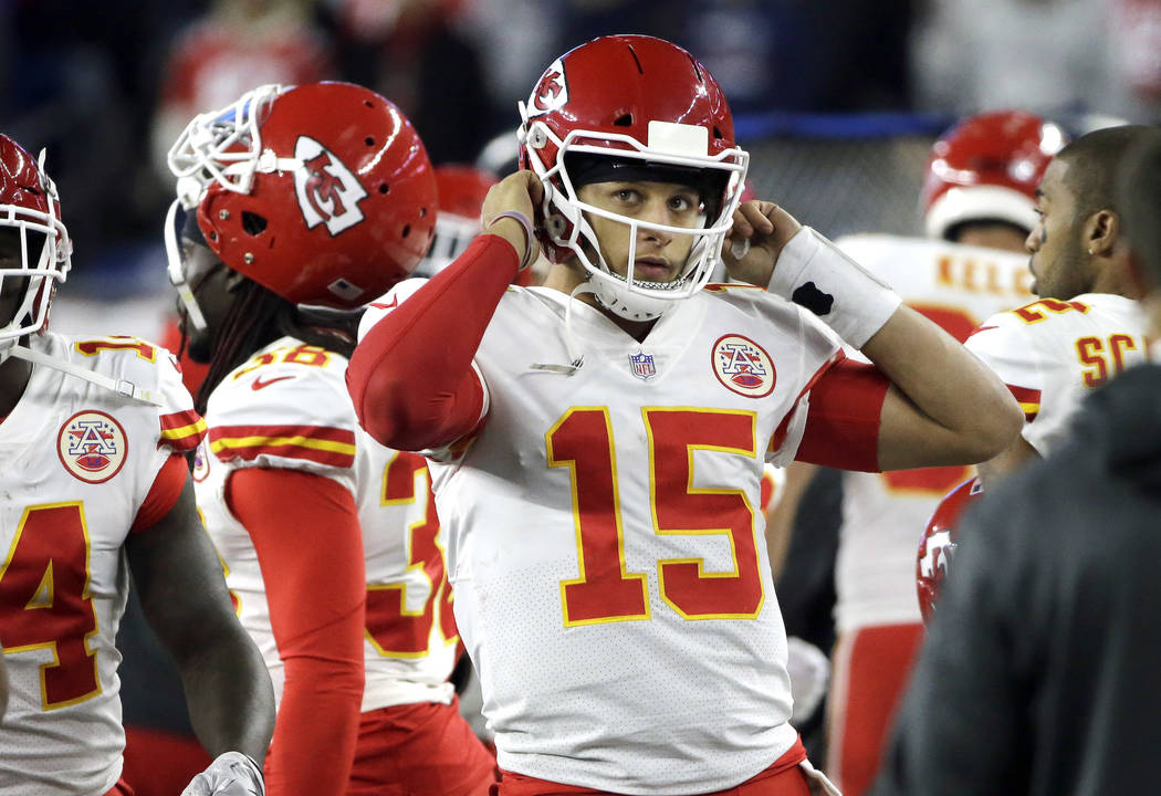 Kansas City Chiefs quarterback Patrick Mahomes removes his helmet on the sideline during the second half of an NFL football game against the New England Patriots, Sunday, Oct. 14, 2018, in Foxboro ...