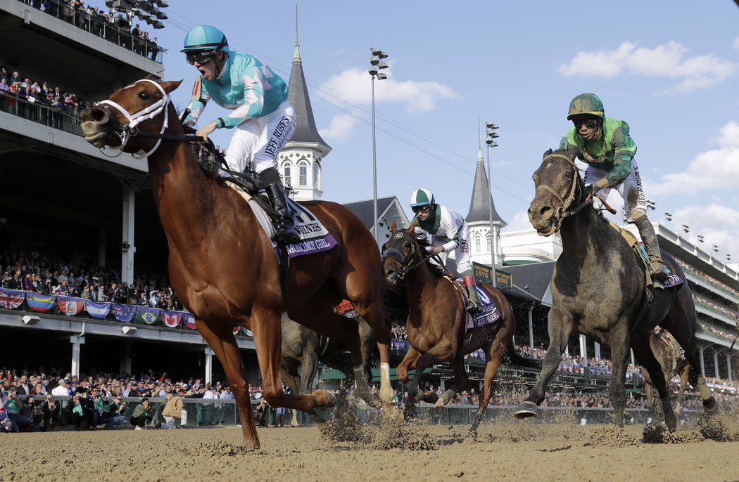 Florent Geroux, left, celebrates as he rides Monomoy Girl to victory as Joe Bravo, center, atop Blue Prize and Jose Ortiz, right, atop Wow Cat follow in the Breeders' Cup Distaff horse race at Chu ...