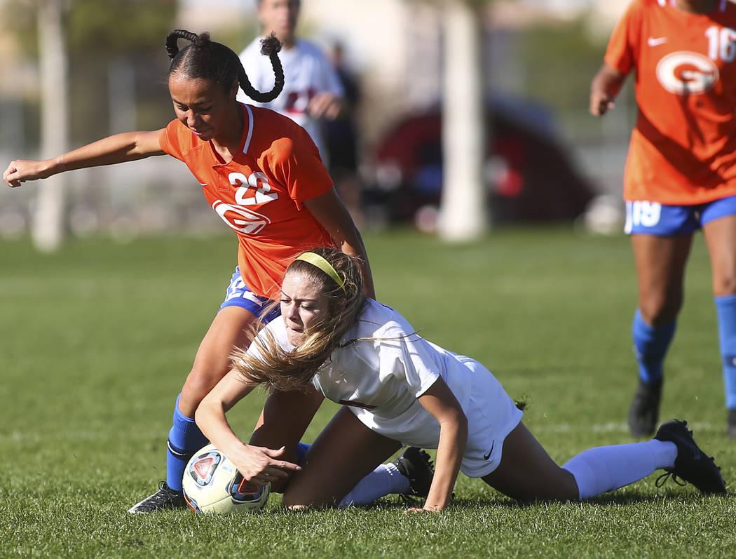 Bishop Gorman's Kennedy Enus (22) battles for the ball against Coronado's Alysa Caso during the Desert Region girls soccer championship game at Bettye Wilson Soccer Complex in Las Vegas on Saturda ...