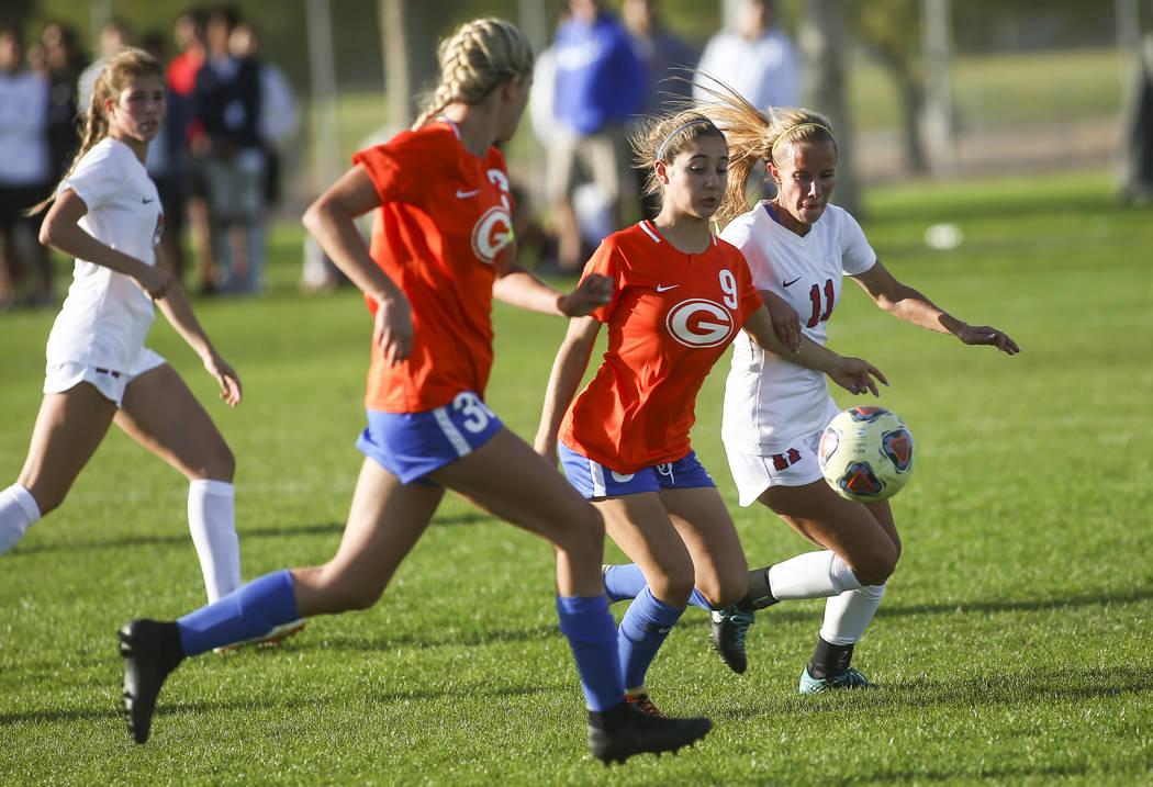 Bishop Gorman's Jaden Terrana (9) moves the ball in front of Coronado's Heather Mitchell during the Desert Region girls soccer championship game at Bettye Wilson Soccer Complex in Las Vegas on Sat ...