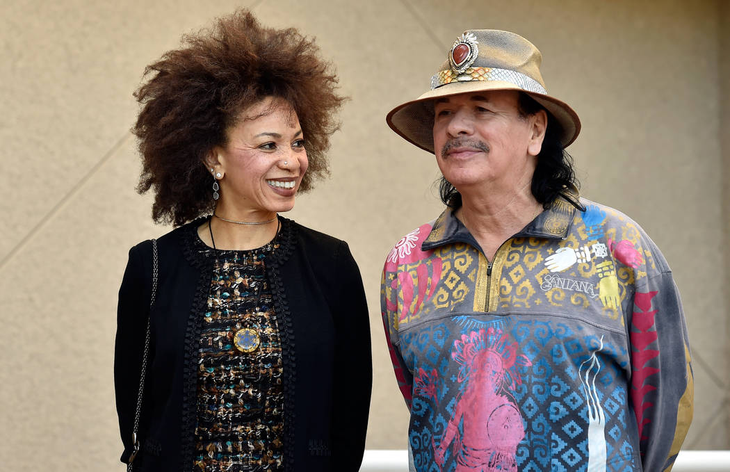 Cindy Blackman Santana, left, and her husband Carlos Santana listen to speakers during the unveiling of a third in a series of benches at the Henderson City Hall Thursday, Nov. 1, 2018, in Henders ...