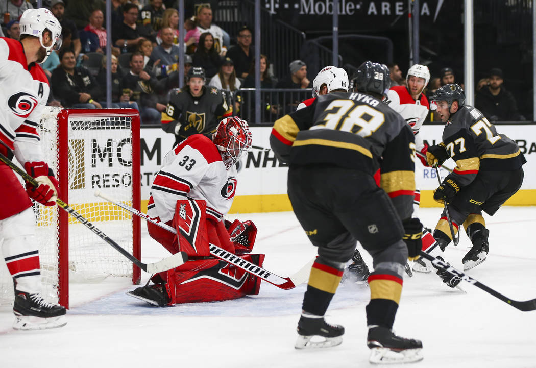 Golden Knights defenseman Brad Hunt (77) sends in a shot past Carolina Hurricanes goaltender Scott Darling (33) to score a goal during the first period of an NHL hockey game at T-Mobile Arena in L ...