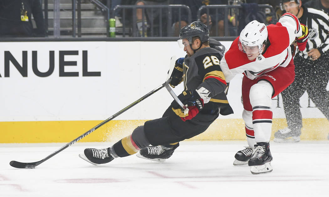 Golden Knights left wing William Carrier (28) gets tripped up by Carolina Hurricanes defenseman Haydn Fleury (4) during the first period of an NHL hockey game at T-Mobile Arena in Las Vegas on Sat ...
