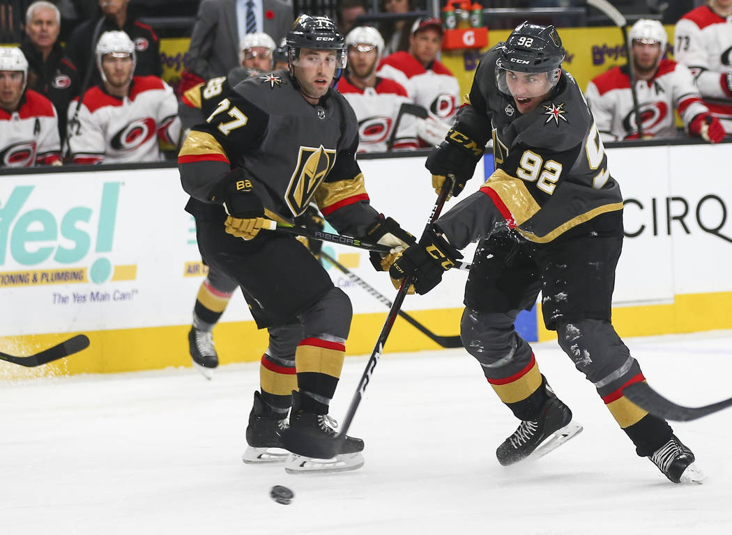 Golden Knights left wing Tomas Nosek (92) shoots against the Carolina Hurricanes as Golden Knights defenseman Brad Hunt (77) looks on during the first period of an NHL hockey game at T-Mobile Aren ...