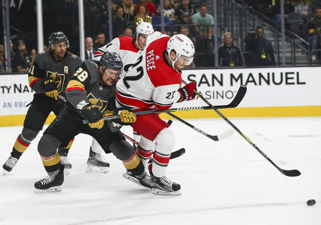 Golden Knights left wing William Carrier (28) battles for the puck against Carolina Hurricanes defenseman Brett Pesce (22) during the first period of an NHL hockey game at T-Mobile Arena in Las Ve ...
