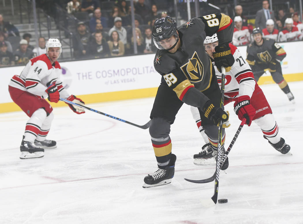Golden Knights right wing Alex Tuch (89) moves the puck past Carolina Hurricanes defenseman Justin Faulk (27) during the first period of an NHL hockey game at T-Mobile Arena in Las Vegas on Saturd ...