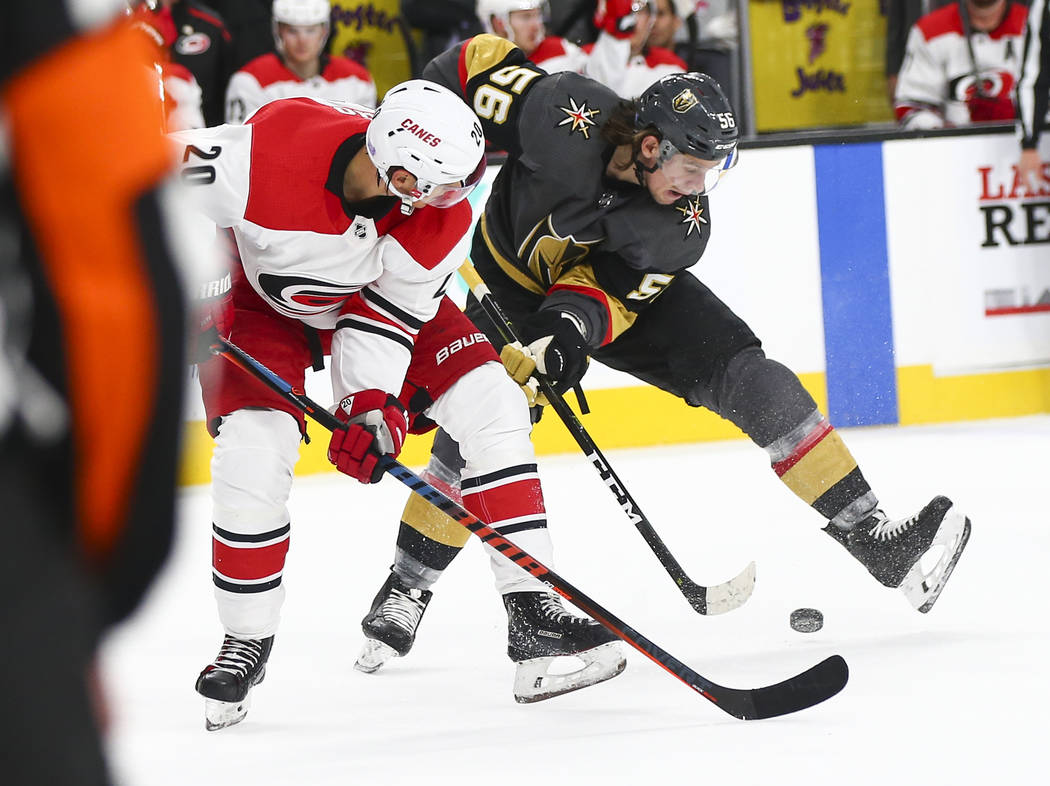 Golden Knights center Erik Haula (56) gets control of the puck over Carolina Hurricanes center Sebastian Aho (20) during the second period of an NHL hockey game at T-Mobile Arena in Las Vegas on S ...