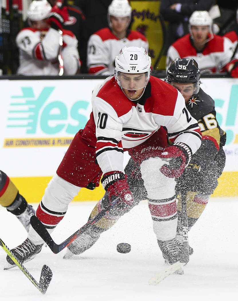 Carolina Hurricanes center Sebastian Aho (20) moves the puck in front of Golden Knights center Erik Haula (56) during the second period of an NHL hockey game at T-Mobile Arena in Las Vegas on Satu ...