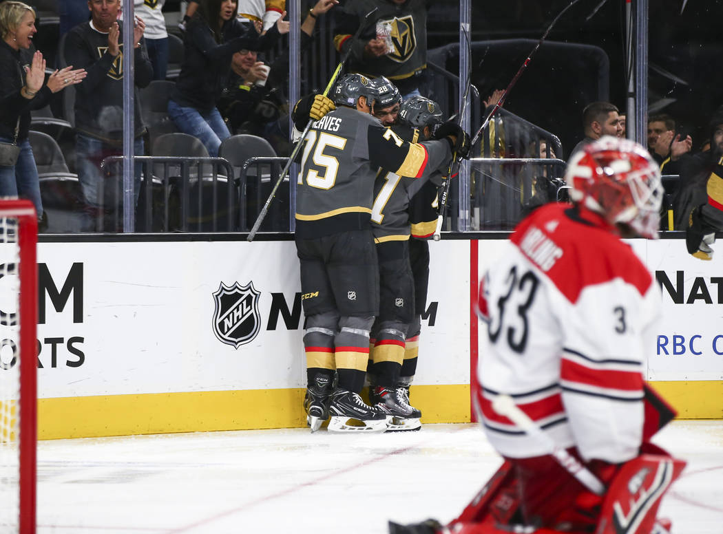Golden Knights left wing William Carrier (28), center, celebrates his goal against Carolina Hurricanes goaltender Scott Darling (33) with his teammates Pierre-Edouard Bellemare (41) and Ryan Reave ...