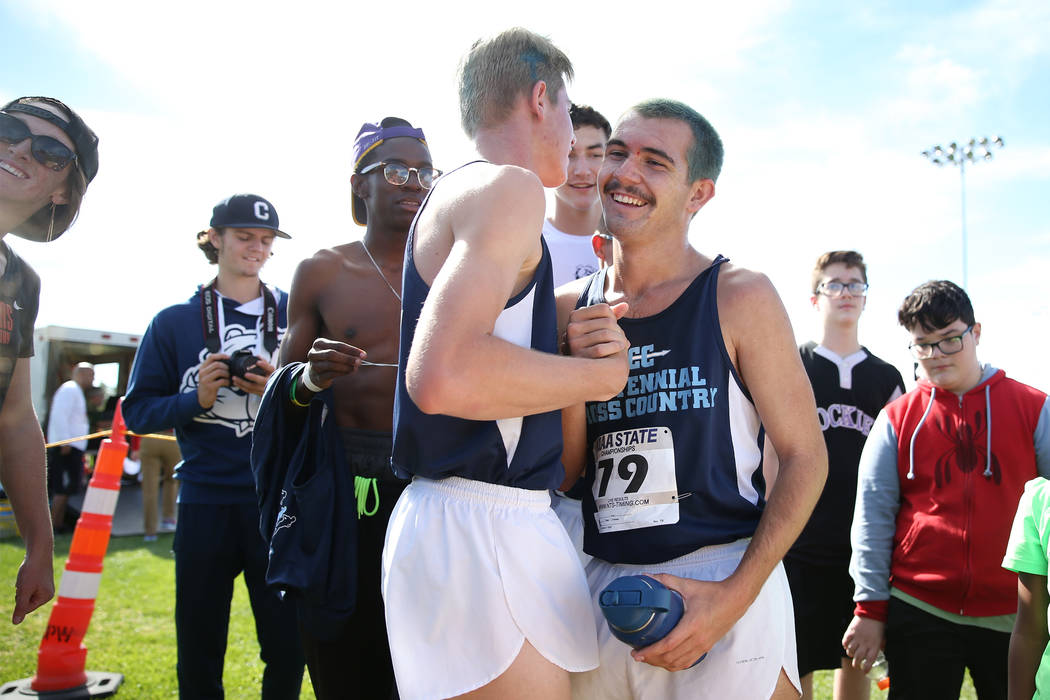 Centennial's Tucker Raymond (81), left, and Alexander Miller (79), embrace after scoring first place in teams during the NIAA 4A Boys Cross Country State Championship at the Veteran's Memorial Par ...