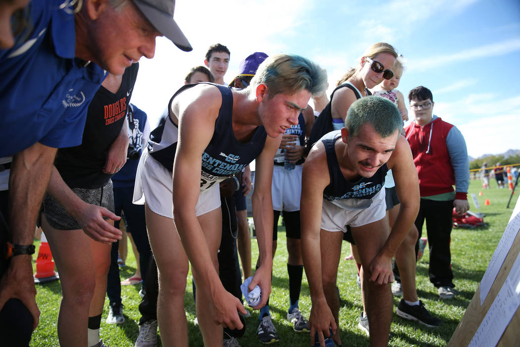 Centennial's Tucker Raymond (81), left, and Alexander Miller (79), check the verified scores for the NIAA 4A Boys Cross Country State Championship at the Veteran's Memorial Park in Boulder City, S ...