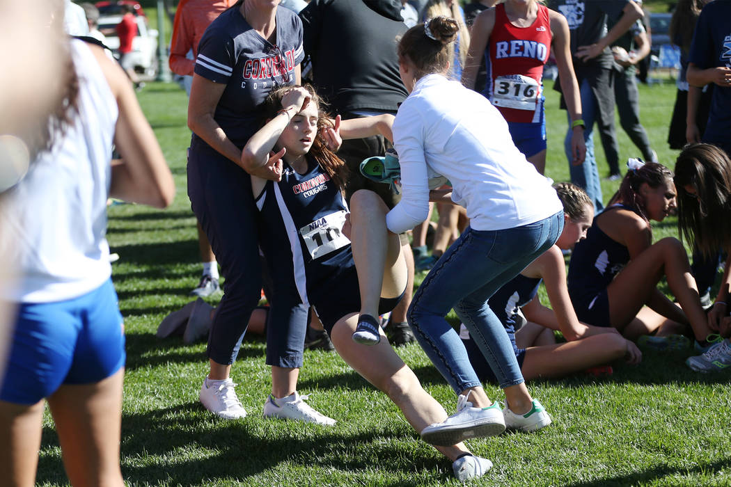 Coronado's junior Claire Rawlins (101) is carried off the finish line area after finishing in 12 place overall in the NIAA 4A Girls Cross Country State Championship at the Veteran's Memorial Park ...