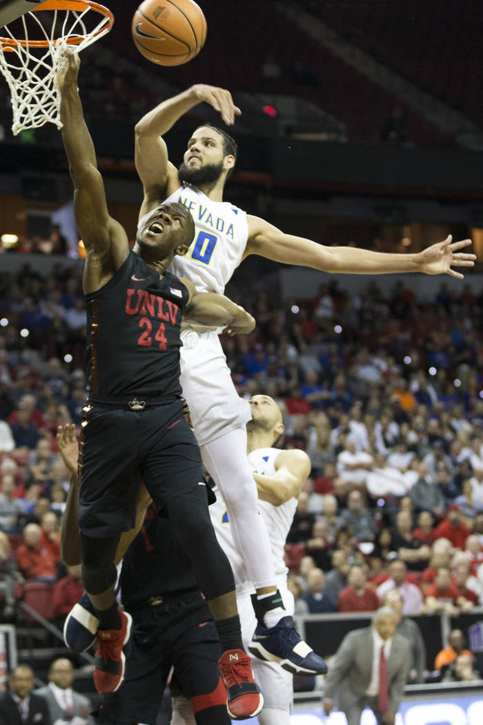 UNLV Rebels guard Jordan Johnson (24) is blocked by Nevada Wolf Pack forward Caleb Martin (10) in the second half of the Mountain West Conference men's basketball tournament game at the Thomas &am ...