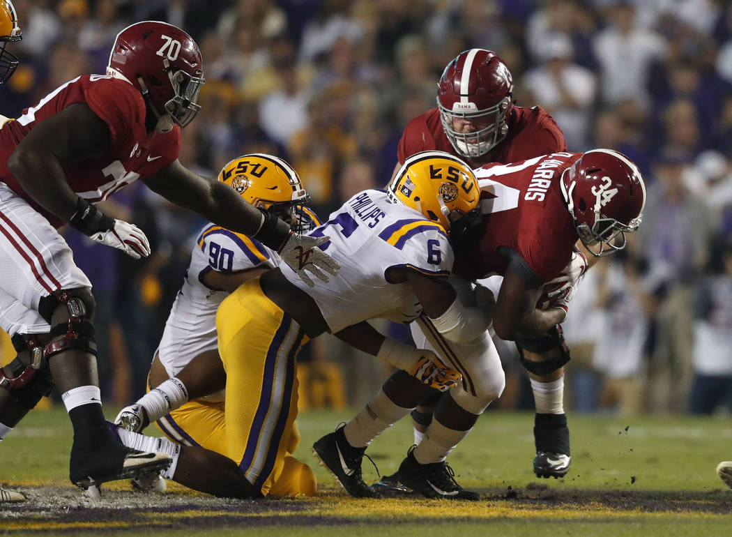 Alabama running back Damien Harris (34) carries against LSU linebacker Jacob Phillips (6) and defensive lineman Stephon Wynn Jr. (90) in the first half of an NCAA college football game in Baton Ro ...