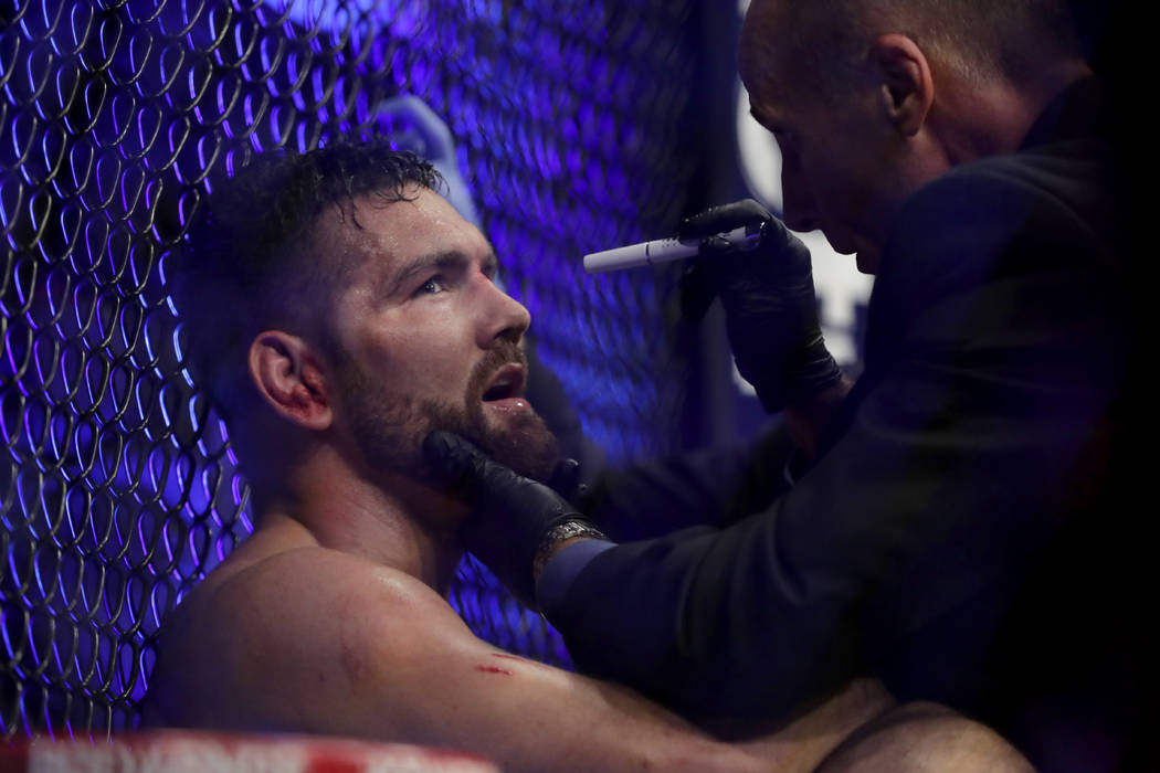 Chris Weidman, left, is examined by a doctor after he lost to Ronaldo Souza during the third round of a middleweight mixed martial arts bout at UFC 230, Sunday, Nov. 4, 2018, at Madison Square Gar ...