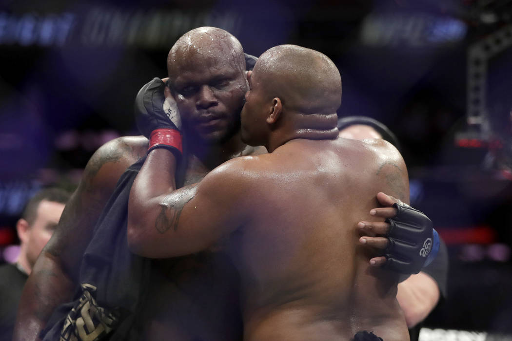 Daniel Cormier, right, gives a kiss to Derrick Lewis after Cormier won their heavyweight mixed martial arts bout by submission in the second round at UFC 230, early Sunday, Nov. 4, 2018, at Madiso ...