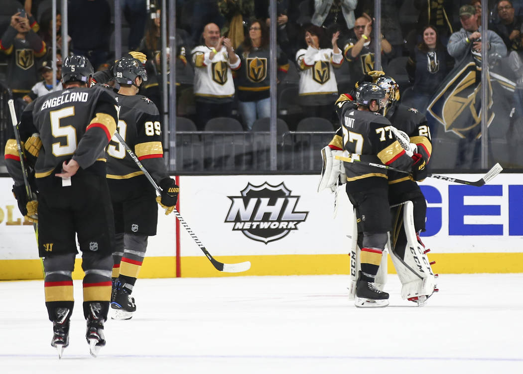 Golden Knights defenseman Brad Hunt (77) celebrates with Golden Knights goaltender Marc-Andre Fleury (29) after the team won 3-0 over the Carolina Hurricanes in an NHL hockey game at T-Mobile Aren ...