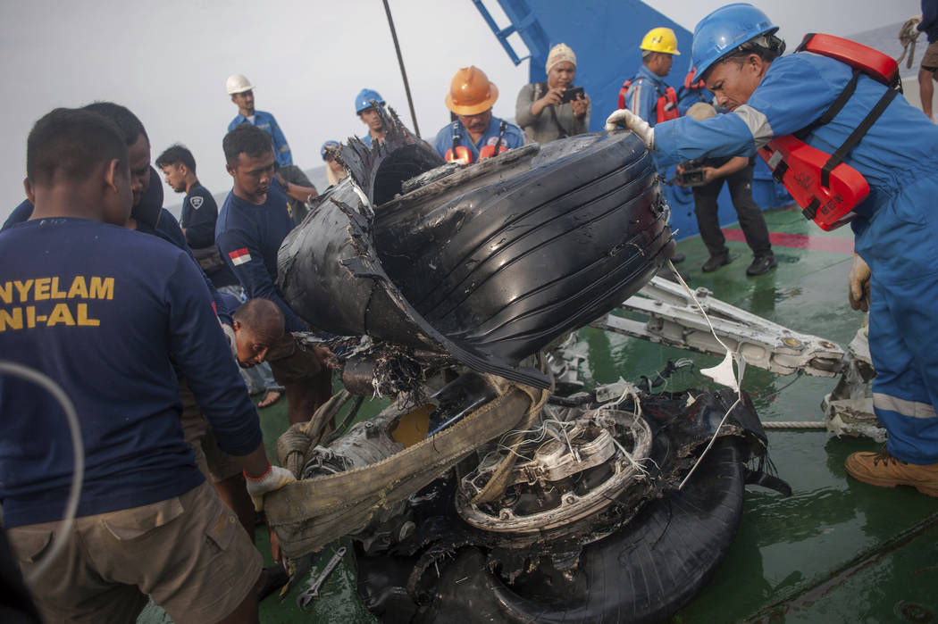 Rescuers inspect part of the landing gears of the crashed Lion Air jet they retrieved from the sea floor in the waters of Tanjung Karawang, Indonesia, Sunday, Nov. 4, 2018. Investigators succeeded ...