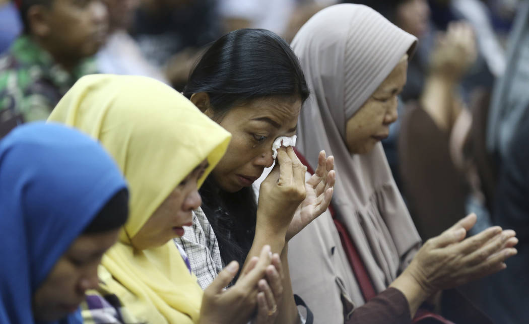 Relatives weep as they pray for victims of the Lion Air jet that crashed into the Java Sea during a press conference in Jakarta, Indonesia, Monday, Nov. 5, 2018. Distraught and angry relatives of ...