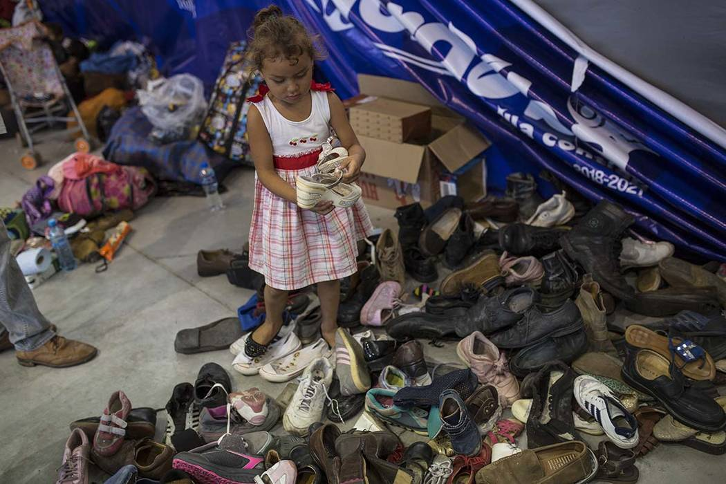 In this Nov. 4, 2018 photo, a girl chooses from donated shoes as members of a U.S.-bound Central American migrant caravan rest at a shelter in Cordoba, Veracruz state, Mexico. The group now finds ...