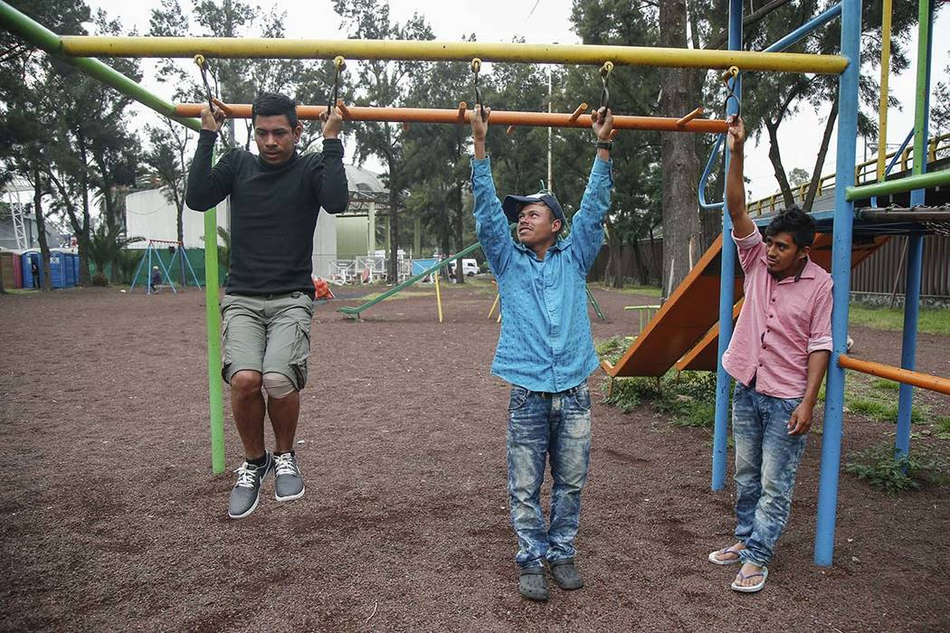 Honduran migrants Izekiel Romero, left, and Juan Carlos Santa Maria, middle, hold a pull-up contest as fellow migrant Wilbar Omar Lara watches, at a sporting center that has been turned into a she ...
