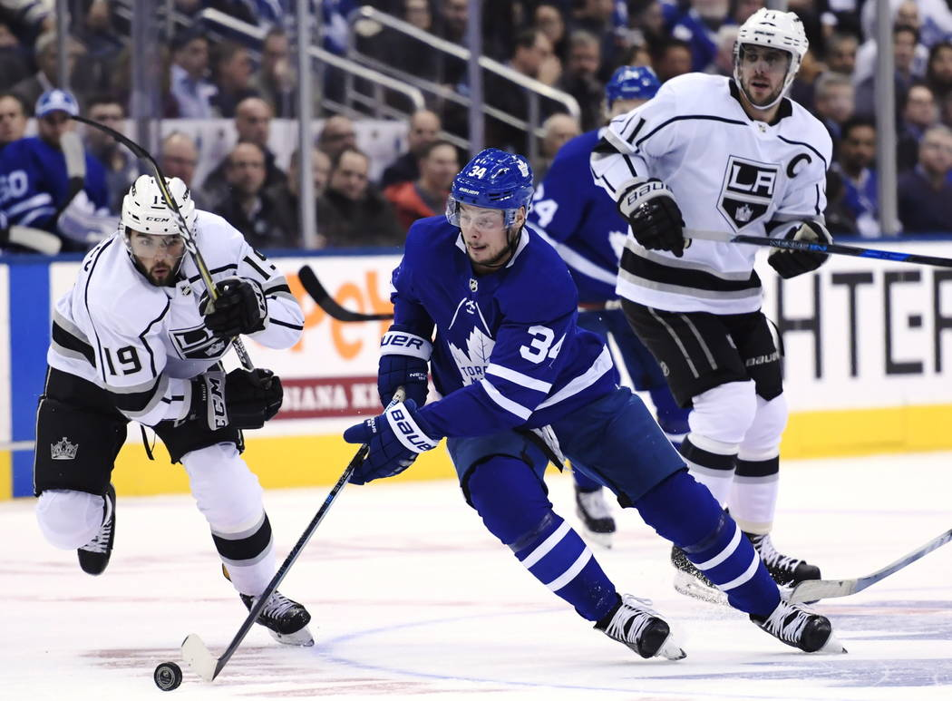Toronto Maple Leafs centre Auston Matthews (34) skates between Los Angeles Kings left wing Alex Iafallo (19) and Kings centre Anze Kopitar (11) during first period NHL hockey action in Toronto on ...
