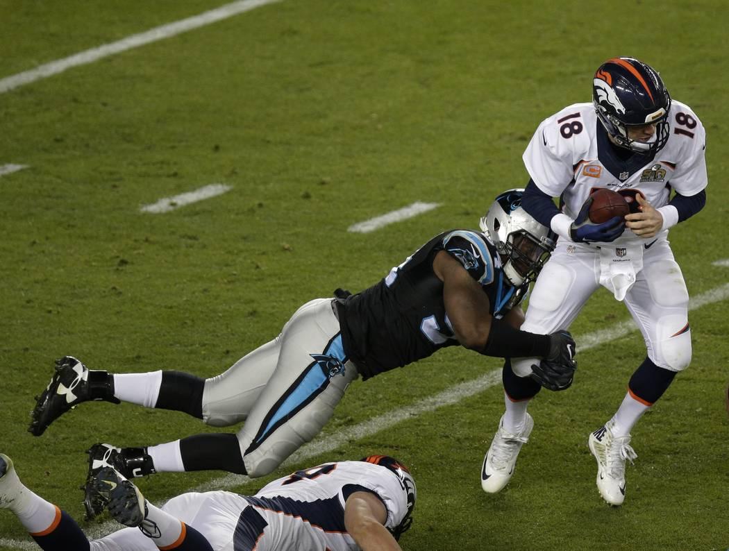 Carolina Panthers Kony Ealy (94) sacks Denver Broncos Peyton Manning (18) during the second half of the NFL Super Bowl 50 football game Sunday, Feb. 7, 2016, in Santa Clara, Calif. (AP Photo/Charl ...