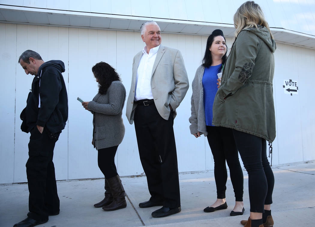 Steve Sisolak, center, Democratic candidate for Nevada governor, with his two daughters Ashley and Carley, wait in line to cast their vote at a polling station at Kenny Guinn Middle School in Las ...