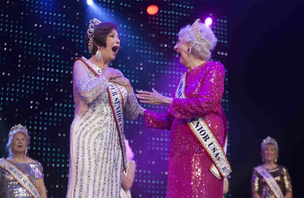 Miss Super Senior Sally Beth Vick reacts after winning Ms. Super Senior Universe next to contestant Miss Senior USA Nancy Long at the Ms. Senior Universe Pageant at the Fabulous Saxe Theatre in La ...