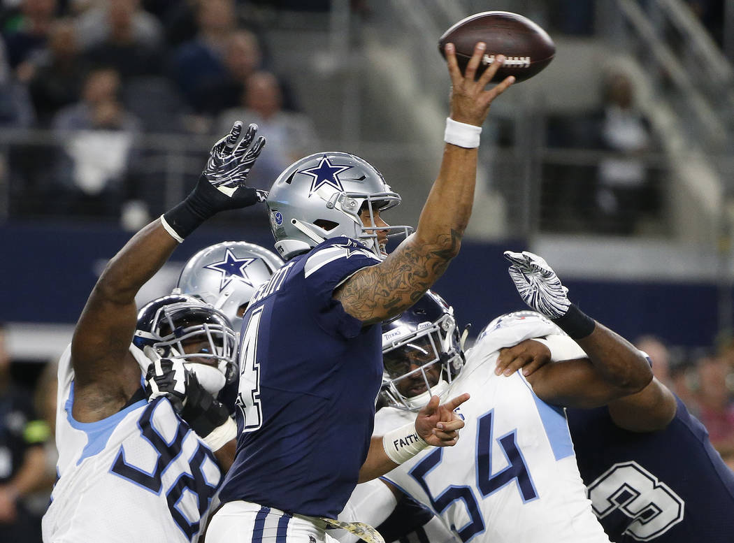 Dallas Cowboys quarterback Dak Prescott (4) works under pressure in the pocket against the Tennessee Titans during the first half of an NFL football game, Monday, Nov. 5, 2018, in Arlington, Texas ...