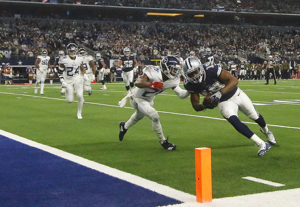 Dallas Cowboys wide receiver Amari Cooper (19) runs into the end zone as Tennessee Titans cornerback Malcolm Butler (21) defends during the first half of an NFL football game, Monday, Nov. 5, 2018 ...