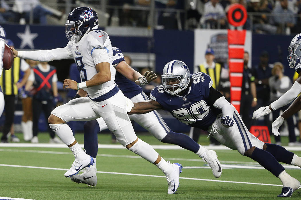 Tennessee Titans quarterback Marcus Mariota (8) runs for a touchdown against Dallas Cowboys defensive end Demarcus Lawrence (90) during the second half of an NFL football game, Monday, Nov. 5, 201 ...