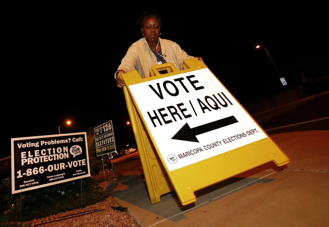 """Maricopa County elections official Deborah Atkins places a """"vote"""" sign outside a polling station prior to it's opening, Tuesday, Nov. 6, 2018, in Phoenix. (Matt York/AP)"""