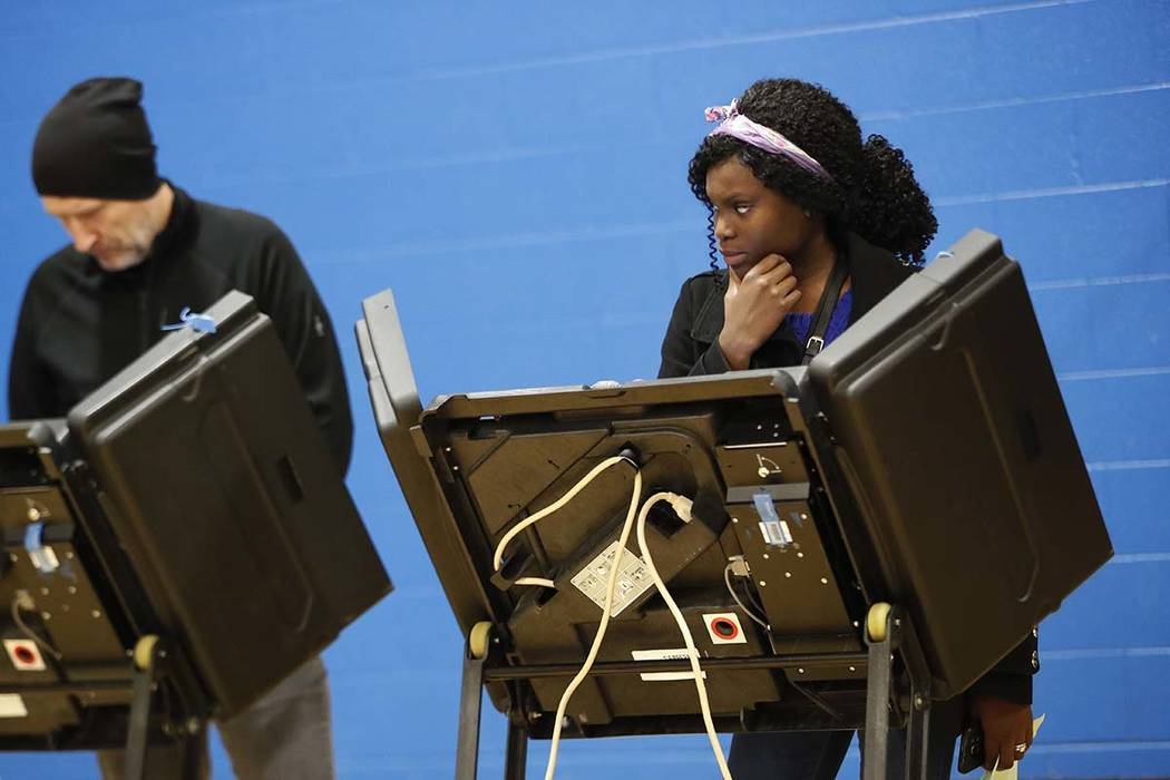 A voter waits for assistance from a volunteer at the Tuttle Park Recreation Center, Tuesday, Nov. 6, 2018, in Columbus, Ohio. Across the country, voters headed to the polls Tuesday in one of the m ...