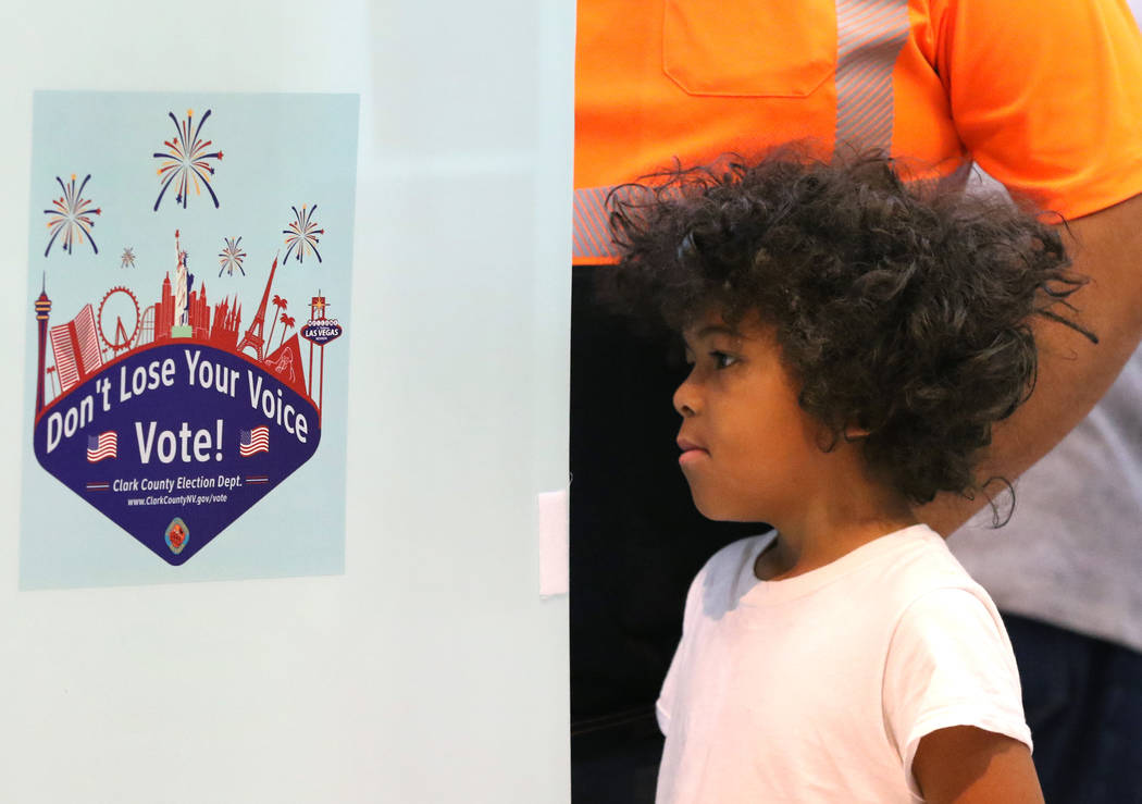 A child watches as his father Luis Aguilera, who declined to give his son's name, casts his ballots at a polling station at Galleria Mall on Tuesday, Nov. 6, 2018, in Henderson. (Bizuayehu Tesfaye ...