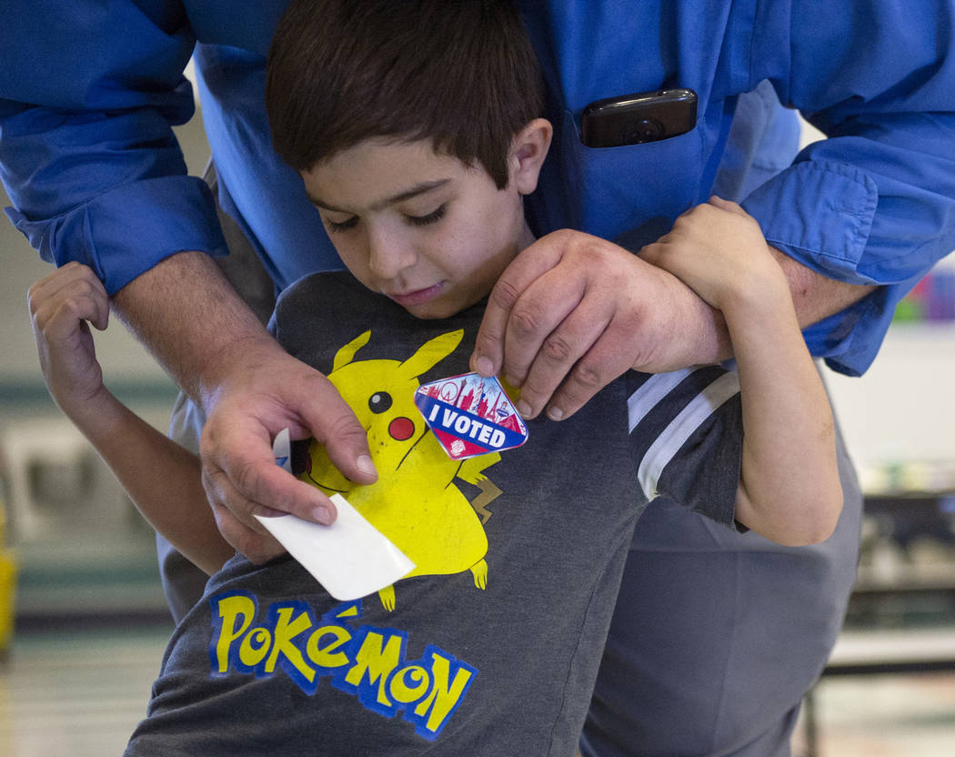Timothy Marshall, 5, gets a voters sticker placed on his shirt by his father, William Marshall, at a polling station at Raul Elizondo Elementary School in North Las Vegas, Tuesday, Nov. 6, 2018. C ...