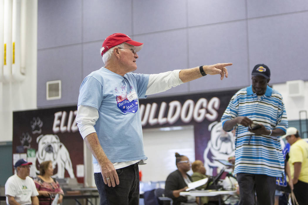Volunteer Ed Bills directs voters to various booths to cast their ballots at a polling station at Raul Elizondo Elementary School in North Las Vegas, Tuesday, Nov. 6, 2018. Caroline Brehman/Las Ve ...