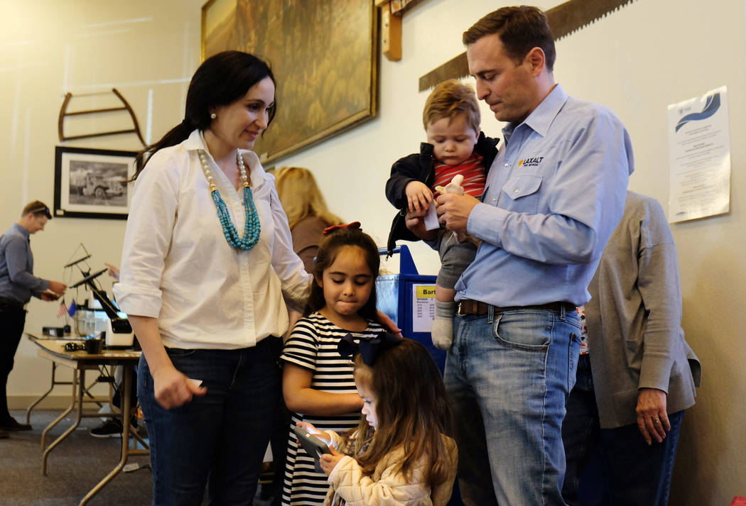 Adam Laxalt, Republican candidate for Nevada governor, holds his son, Jack, before voting at Bartley Ranch Regional Park in Reno, Tuesday, Nov. 6, 2018. His wife, Jamie, older daughter Sophia and ...