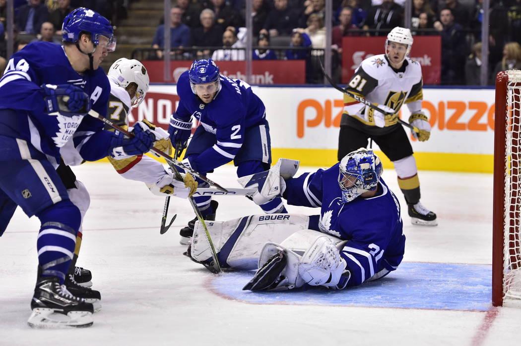 Vegas Golden Knights center William Karlsson (71) and Toronto Maple Leafs defensemen Morgan Rielly (44) and Ron Hainsey (2) battle in front of Maple Leafs goaltender Frederik Andersen (31) during ...