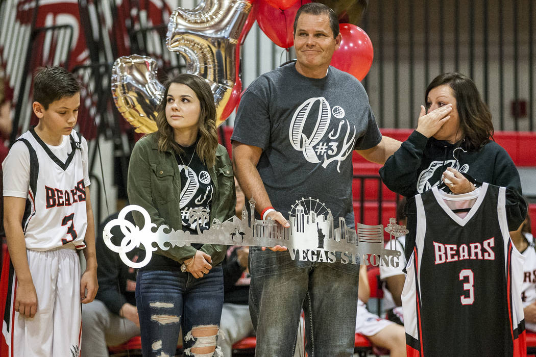 The Robbins family, from left, Quade, Skylar, Joe and Tracey, receives a key and a retired No. 3 jersey during a ceremony to remember Quinton Robbins, a victim of the Oct. 1, 2017, shooting, at th ...