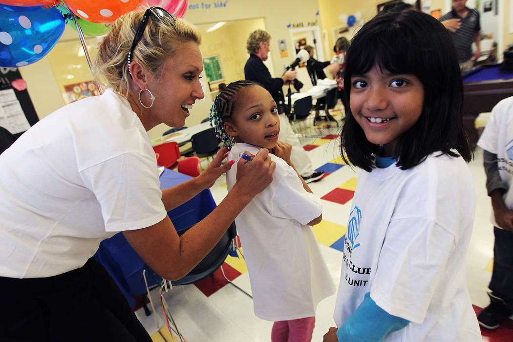Professional golfer and Henderson resident Natalie Gulbis, left, signs autographs for Fendi Davis, middle, and Darlene Funes as she opens a new Boys and Girls Club at the Apache Pines Apartment Co ...