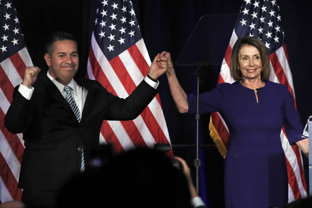 DCCC Chair Ben Ray Luján, left, and House Democratic Leader Nancy Pelosi of Calif., gesture to a crowd of volunteers and supporters of the Democratic party at an election night event at the H ...