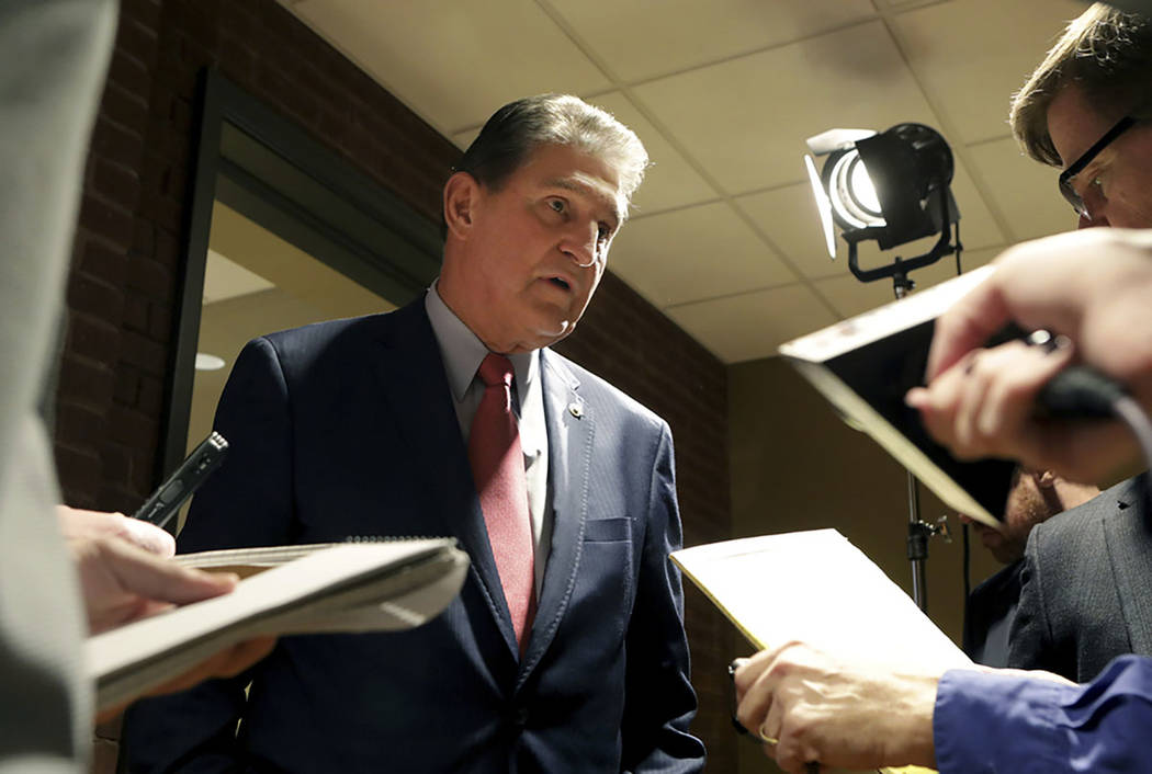 Sen. Joe Manchin speaks to reporters after a debate with Patrick Morrisey in Morgantown, W.Va., on Nov. 1, 2018. (AP Photo/Raymond Thompson)