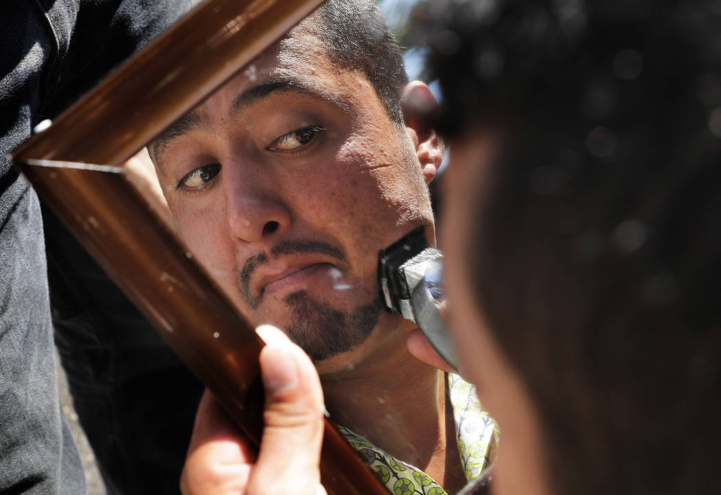 A Central American migrant trims his facial hair in a shelter at the Jesus Martinez stadium in Mexico City, Tuesday, Nov. 6, 2018. Humanitarian aid converged around the stadium in Mexico City wher ...