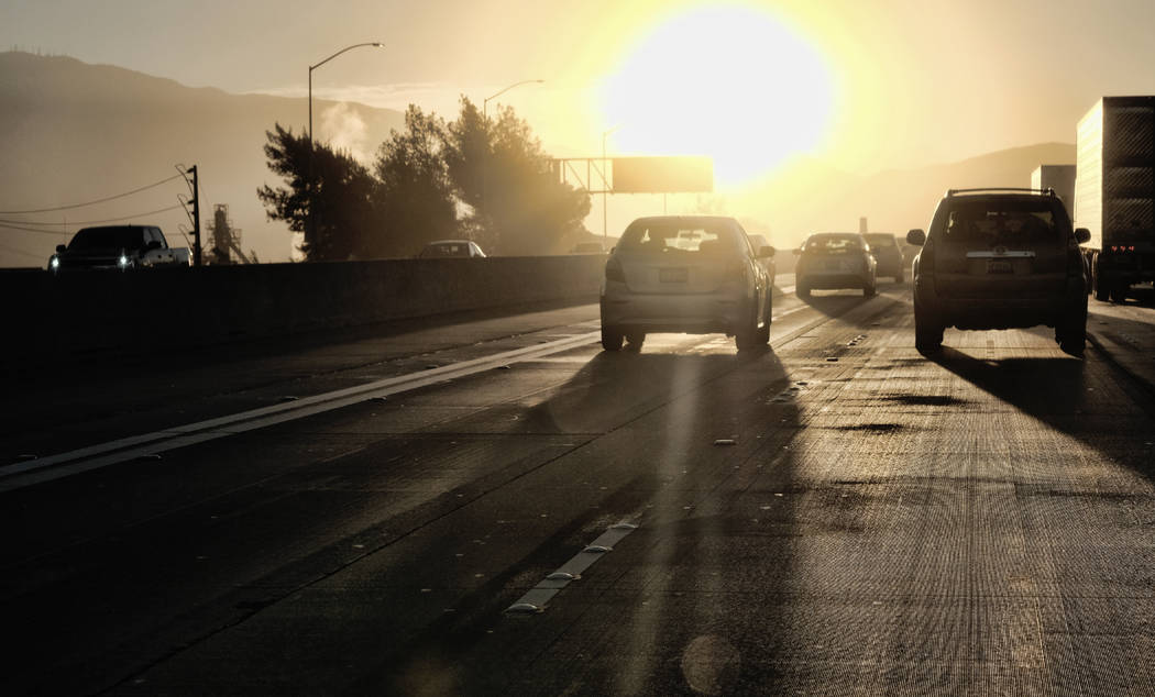 In this Aug. 31, 2018, 2018 photo morning commuters drive into downtown Los Angeles as the sun rises along Interstate 5. It's clockwork: Every fall and spring, Californians and the rest of the nat ...