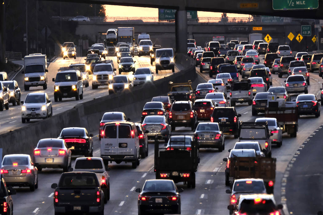 FILE - In this Nov. 15, 2016 file photo morning rush hour traffic makes it's way along US 101 near downtown Los Angeles. If voters approve Proposition 7 on Nov. 6, that would pave the way for year ...